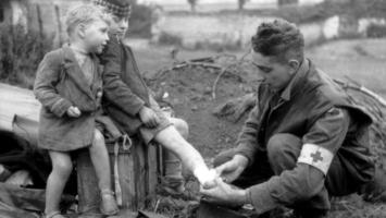 Un adolescent soigne le pied d'un enfant